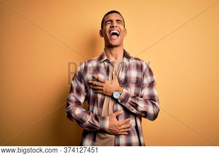 Young handsome african american man wearing casual shirt standing over yellow background smiling and laughing hard out loud because funny crazy joke with hands on body.