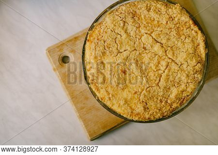 Hungarian-style Crumble Pie With Cheesecake Feeling In A Glass Fire-resistant Bowl On A Wooden Board
