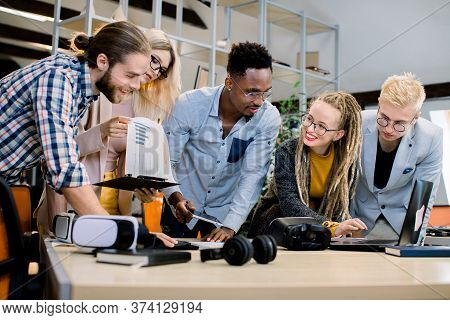 Multiethnic Group Of Happy Young Business People Working Together In Office. Laptop, Vr Goggles