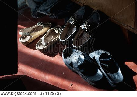 Old Shoes In The Beam Of Light. A Lot Of Old Shoes In A Dark Room. Creative Concept.