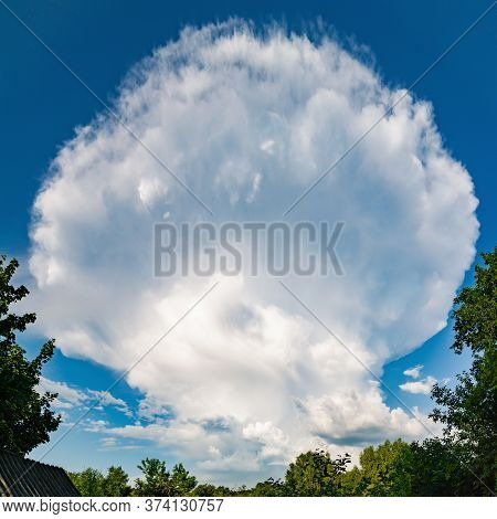 Huge Thundercloud. A Large Storm Cloud In The Shape Of A Huge Mushroom. Natural Weather Events.
