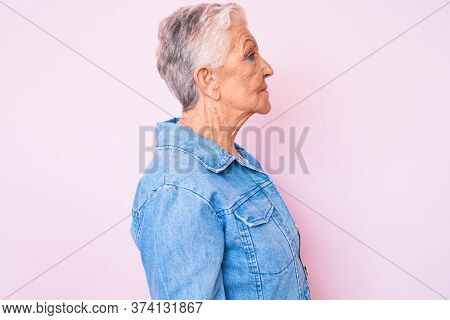 Senior beautiful woman with blue eyes and grey hair wearing casual denim jacket looking to side, relax profile pose with natural face with confident smile.