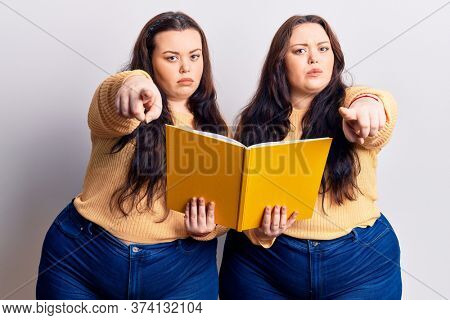 Young plus size twins holding book pointing with finger to the camera and to you, confident gesture looking serious