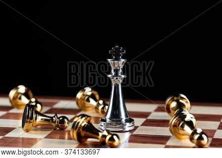 Silver King Chess Defeats Gold Pawns On Wooden Chessboard. Intellectual Duel And Tactical Battle In