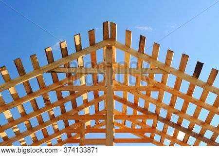 Fresh Wooden Yellow Rafters On A Background Of Blue Sky. The Construction Of The Pitched Roof Of A R