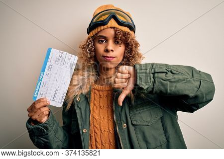 Young african american tourist woman wearing ski goggles holding plane boarding pass tickets with angry face, negative sign showing dislike with thumbs down, rejection concept