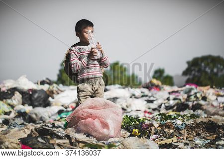 A Poor Boy Collecting Garbage Waste From A Landfill Site In The Outskirts, The Lives And Lifestyles