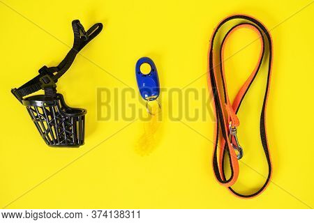 Top View Of Black Plastic Muzzle, Blue Clicker And Orange Collar Or Leash For A Dog On A Yellow Back