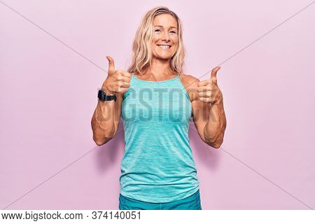 Middle age caucasian blonde woman wearing sports clothes over pink background success sign doing positive gesture with hand, thumbs up smiling and happy. cheerful expression and winner gesture.