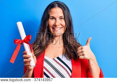 Young beautiful brunette smart woman holding graduated degree diploma over blue background smiling happy and positive, thumb up doing excellent and approval sign
