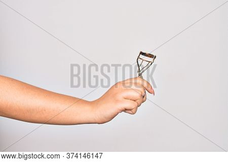 Hand of caucasian young woman holding eyelash curler over isolated white background