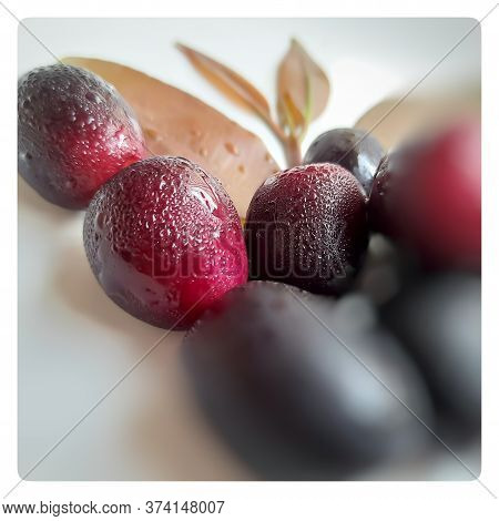 Colorful Black Plum And Some Pink Color Plum With Its Leaf Arranged Beautifully Like Butterfly Shape