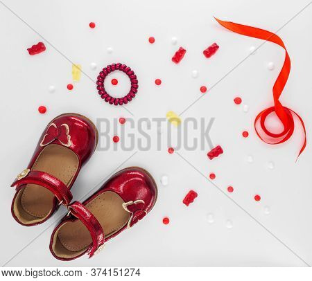 Flat Lay With Red Patent Leather Childrens Shoes With Red Butterfly And Clasps Fasteners And With Wh