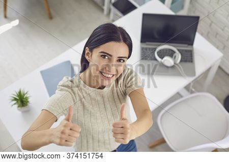 Young Smiling Female Blogger Showing Thumbs Up, View From Above. Product Or Service Advertising.