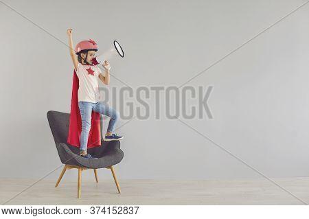 Cute Little Girl In Superhero Costume Shouting In Megaphone On Grey Background. Child With Loudspeak