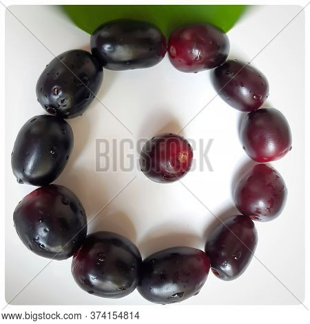 Black Plum Arranged Beautifully In Round Shape Ad One Plum In Center Kept In White Paper Contains Vi