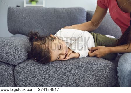 Young Mother Near Her Cute Sleeping Daughter On Sofa At Home. Parent Watching Lovely Child Taking Da