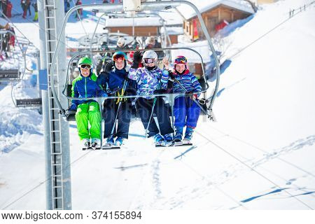 Group Of Skiers Children Sit On Chairlift And Wave Hands Going On The Mountain To Ski, Sitting Toget