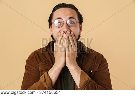 Image of young astonished man in eyeglasses expressing surprise on camera isolated over beige background