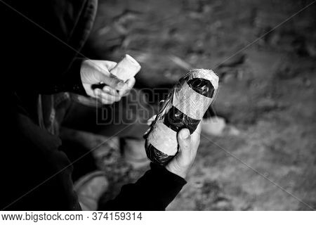 Dealer Is Holding Drug Bag And Money In His Hand On A Black Background.