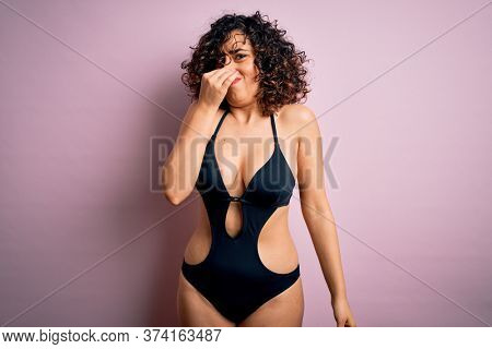 Young beautiful arab woman on vacation wearing swimsuit and sunglasses over pink background smelling something stinky and disgusting, intolerable smell, holding breath with fingers on nose. Bad smell