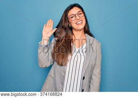 Young hispanic business woman wearing glasses standing over blue isolated background Waiving saying hello happy and smiling, friendly welcome gesture