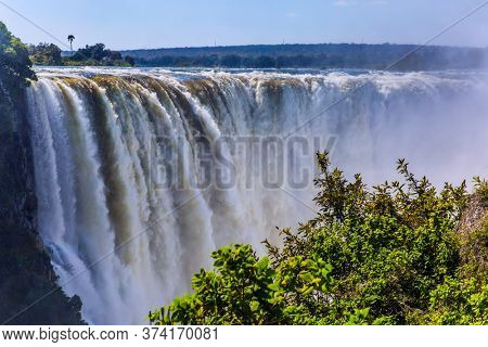 Grand and deep Victoria Falls after the rainy season. Victoria National Park, the Zambezi River. Journey after the wet season. Concept of extreme and photo tourism