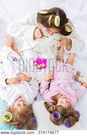 Mother And Two Daughters Are Putting Cucumbers On Eyes With Curlers In Hair Lying On The Bed In The