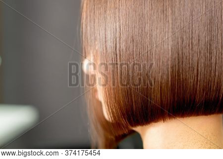 Close-up Of Hairdresser Hand Is Combing Short Hair Of Woman In Hair Salon.