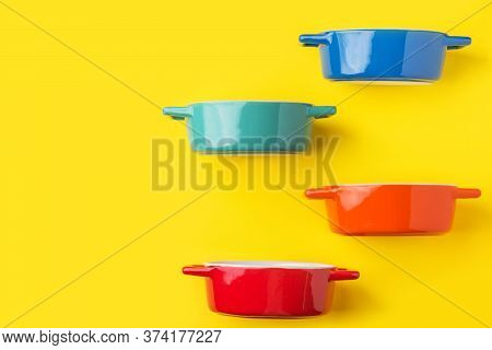 Set Of Multicolored Ceramic Cooking Pots Tureens Cocottes On Bright Yellow Background. Kitchen Utens