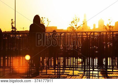 Man Silhouette Near Portable Welded Steel Frame Fences On The Street To Control Crowd Flow