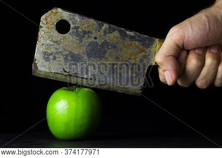 Green Apple On A Black Background. Hand Holds A Kitchen Hatchet Over An Apple. Hatchet Old With Rust
