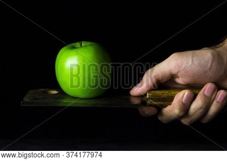 Green Apple On A Black Background. An Apple Is Standing On A Kitchen Hatchet. Hatchet Old With Rust
