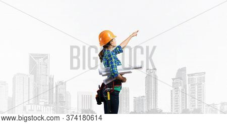 Female Engineer In Hardhat Standing With Technical Blueprints And Pointing Upwards. Side View Of Wom