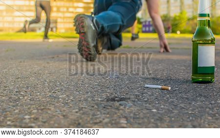 A Discarded Cigarette Lies Near A Beer Bottle On The Asphalt Path Next To A Man Who Is Preparing To