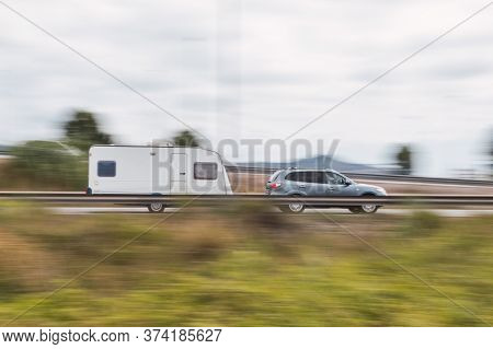 Panning Of A Silver Car With Caravan (trailer) On A Road, Motorway, Movement Effect