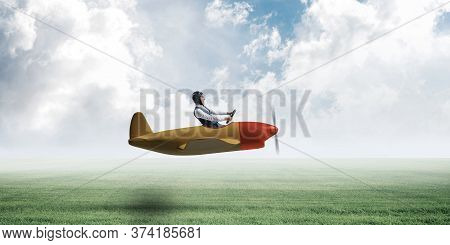 Happy Aviator Driving Small Propeller Plane On Background Of Natural Landscape. Man In Airplane Flyi