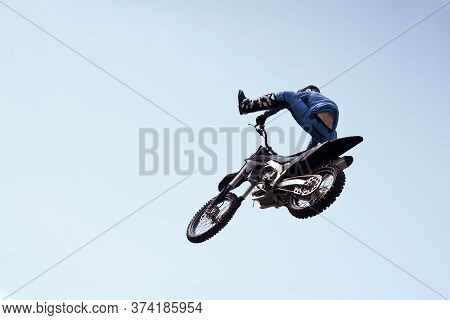 Rider In A Helmet Performs A Risky Stunt In The Air On A Motorcycle