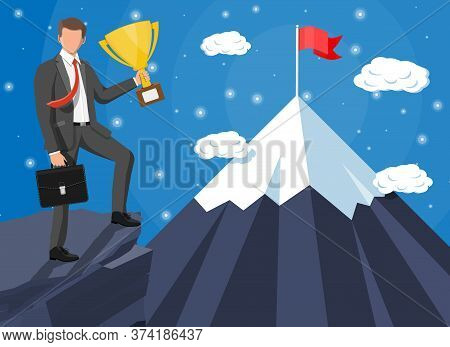 Businessman Standing On Top Of Mountain With Flag And Trophy. Symbol Of Victory, Successful Mission,