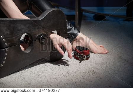 Female Hands In Wooden Shackles During Role-playing Games. Shameful Pillar And Leather Cuffs For Sex
