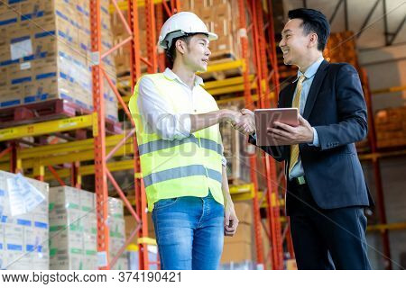 Portrait of asian businessman warehouse owner shake hand with warehouse engineer manager inside distribution warehouse. Business distribution warehouse and inventory inspection concept.