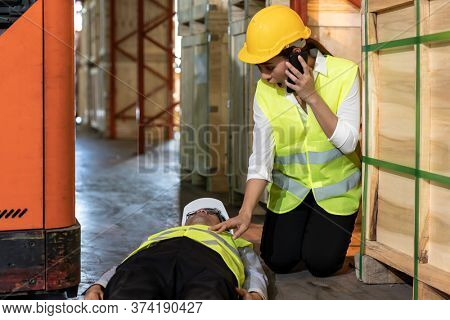 Asian worker Call an ambulance after warehouse manager lying down on warehouse floor after accident from forklift. Using for safety first and business insurance concept.