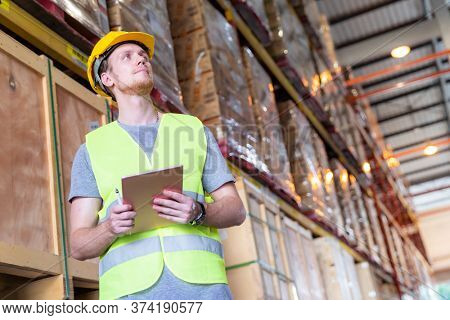 Portrait white caucasian warehouse worker stand with digital tablet for inventory checking in large warehouse distribution center. Reopening  Business warehouse technology and logistic concept