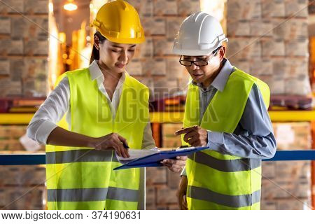 Asian warehouse manager discuss with warehouse worker using archboard to assign job with distribution warehouse in background. Reopening business warehouse technology and logistic concept.
