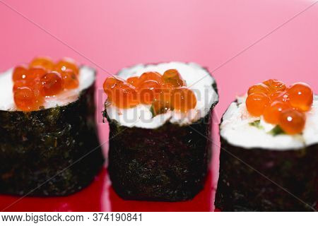 Close Up Of Sushi Roll On The Red Background , Eating Sushi Roll In Restaurant, Sushi Rolls With Cav