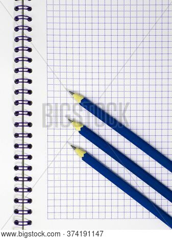 Three Blue Pencils On White Notepad In The Cage With Blue Spiral Wire Binding