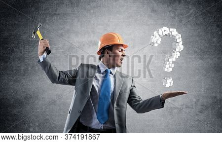 Furious Businessman Going To Crash With Hammer Question Mark. Young Handsome Man In Business Suit An