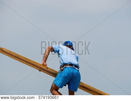 Construction Worker Or Carpenter Carrying Roof Rafters To Build Or Repair A Roof.