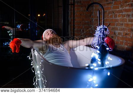 Humorous Image Of An Evil Santa Claus Taking A Bath With Christmas Lights. A Man With A Red Beard In