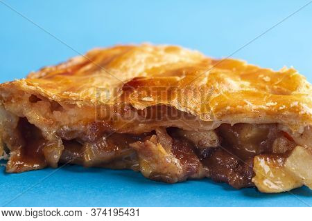 Close-up With A Slice Of Apple Pie Freshly Baked. Home-baked Pie. Apple Pie With A Delicious Golden